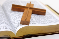 Wood cross laying on an opened Bible.